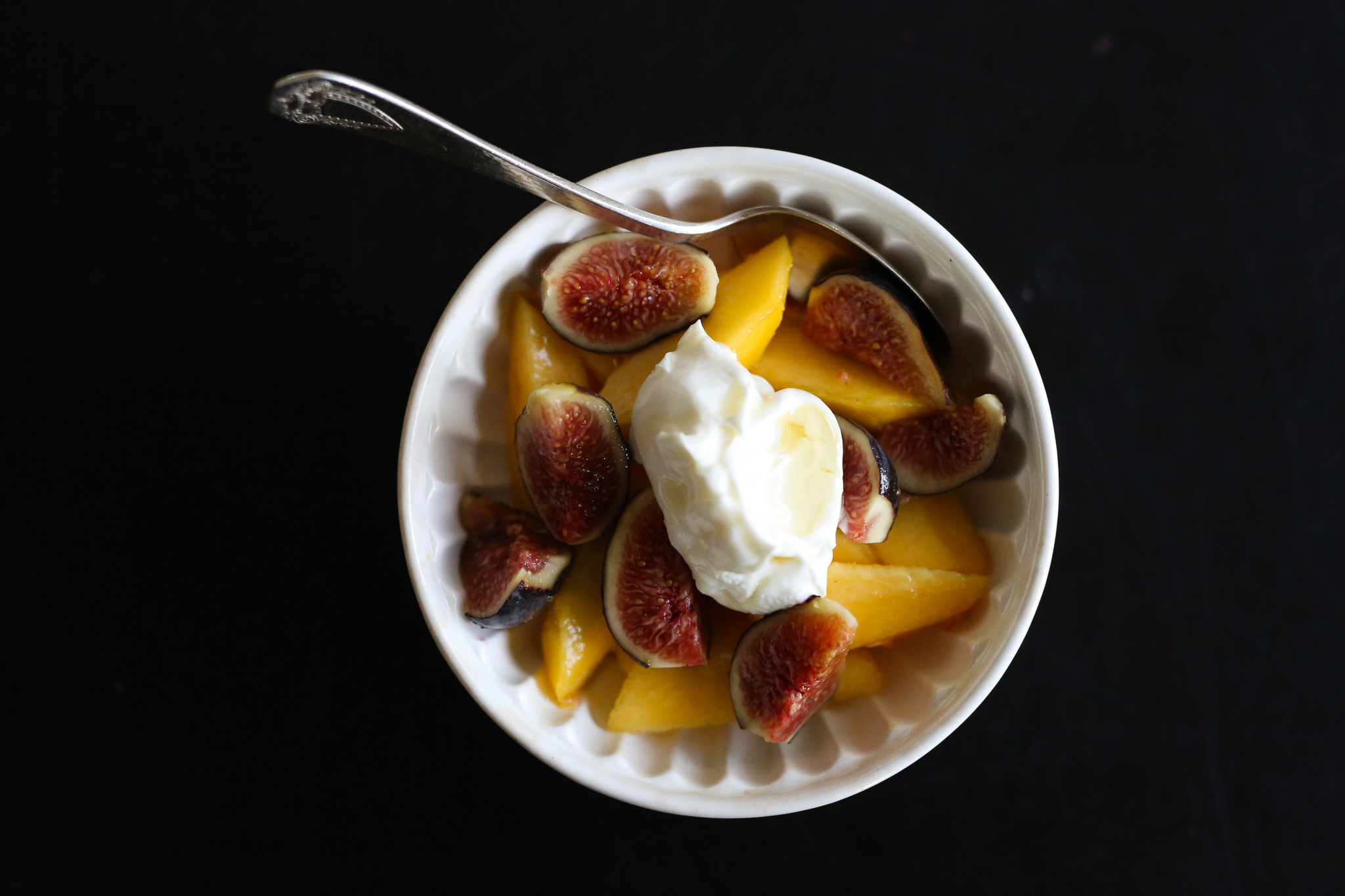 white bowl of peaches and figs with labneh and honey, with silver spoon, on black table
