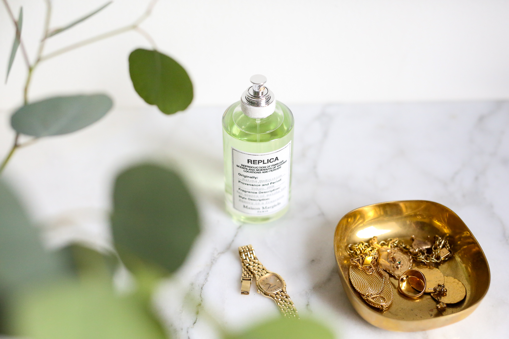 bottle of Matcha Meditation by REBPLIC perfume on marble counter with green leaves, gold watch, and gold tray filled with gold jewelry